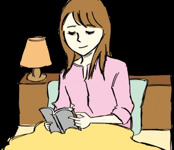 寝る前の時間をベッドで読書をして楽しんでいる女性